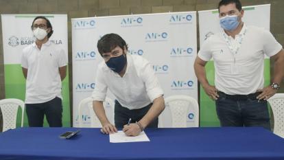El alcalde Jaime Pumarejo firma el convenio con la empresa Air-e. Lo observa el gerente del operador, John Jairo Toro.