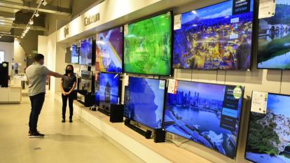 Un comprador en una sección de electrónicos en un establecimiento comercial.