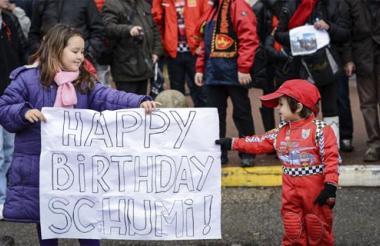 Dos niños sujetan un cartel en el que felicitan al expiloto alemán Michael Schumacher por su 45 cumpleaños, frente al hospital francés de Grenoble.
