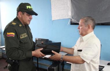El teniente coronel Wilmer Valencia hace entrega de los equipos recuperados al rector del plantel educativo.