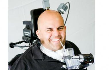 """Usando un brazo robótico controlado por el cerebro, Erik Sorto logra tomar un bebida. """"Este estudio ha sido muy significativo para mí""""."""