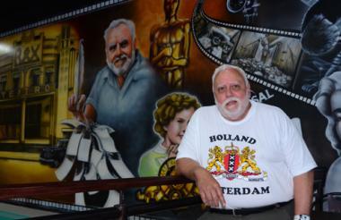 El historiador José Nieto Ibáñez posa junto a su retrato, eje principal del mural obra del artista Samuel Pacheco.