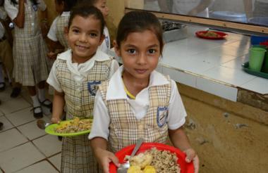Dos estudiantes residentes en Palmar de Varela muestran los alimentos suministrados por el operador Fundasalud.