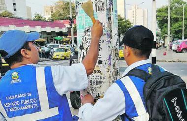 Funcionarios del Distrito quitando publicidad.