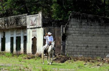 En su caballo, un hombre avanza cerca a las casas destruidas de lo que fue Armero.
