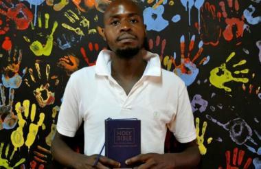 David Ochar, el predicador keniata de la primera iglesia para homosexuales de Kenia, la Cosmopolitan Affirming Church, situada en la capital de Naorobi, posa junto a su Biblia.