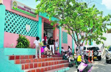 Alumnos del colegio en la puerta principal saliendo de su jornada académica a mediodía.