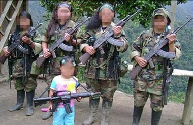 Niñas reclutadas por la guerrilla de las Farc posando con fusiles de combate.