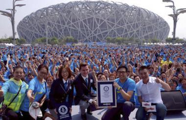 Bailarines posan con los funcionarios de Guinness World Records fuera del Estadio Nacional, también conocido como el Nido de Pájaro, en Beijing