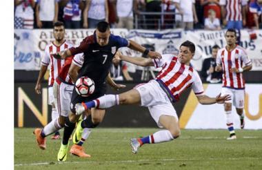El estadounidense Bobby Wood (i) disputa un balón con el centrocampista Rodrigo Rojas de Paraguay .