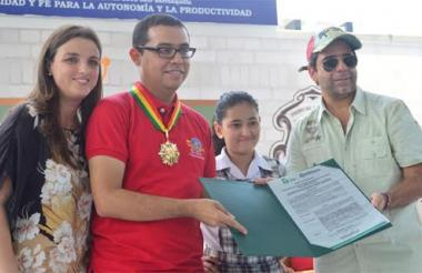 El alcalde Char entrega el reconocimiento al docente Fabián Padilla. Los acompañan la secretaria de Educación, Karen Abudinén, y la estudiante Andrea Franco.