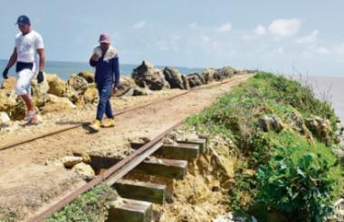 Dos hombres caminan por un tramo de la línea férrea deteriorada en el tajamar.