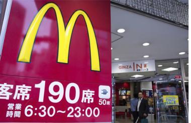 Un empresario camina fuera de un restaurante McDonal's en Tokio, Japón.