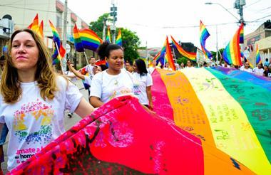 Mujeres sostienen la bandera de la comuinidad LGBTI en una marcha.