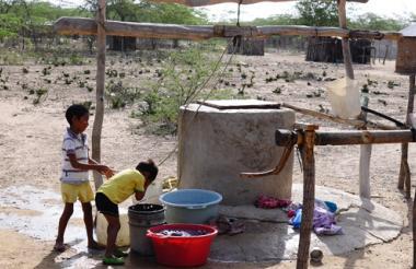 Dos niños wayuu sacan agua de un pozo artesanal en una de las rancherías en la Alta Guajira.