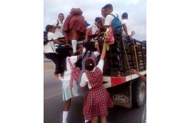 Varios estudiantes tratan de lograr un cupo en esta camioneta que viaja a Maicao.