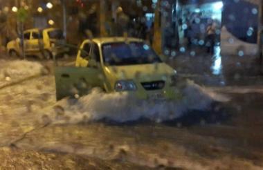 Un taxista desafía la corriente de un arroyo en plena lluvia.