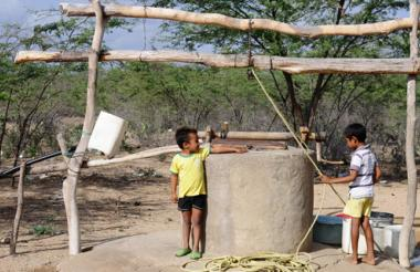 Dos niños wayuu sacan agua de un pozo artesanal en zona rural de Maicao, La Guajira.