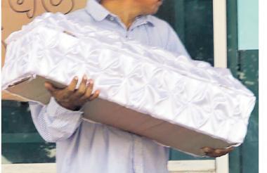 Un hombre sostiene el ataúd del menor fallecido.