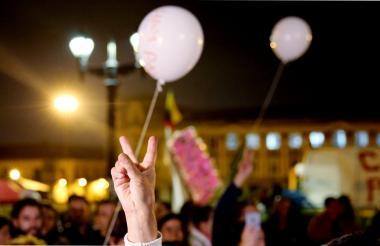 """Un ciudadano levanta la mano haciendo la """"V"""" en señal de victoria, durante la masiva concentración en la Plaza de Bolívar tras los acuerdos de paz."""