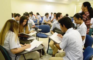 Durante el desarrollo de una de sus clases, el estudiante de medicina Jonathan Leiva revisa sus apuntes junto a sus compañeros del salón.