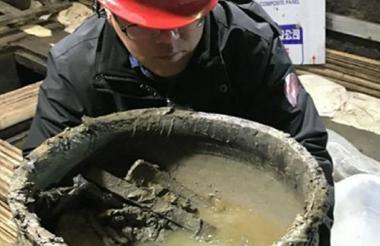 Arqueólogo chino carga el recipiente que contiene la sopa.