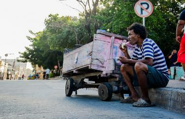 Un habitante de la calle come en un andén.