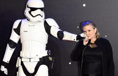"""Carrie Fisher posando junto a un personaje de la película durante el preestreno europeo de """"Star Wars: El Despertar de la Fuerza"""" en Londres, Reino Unido."""