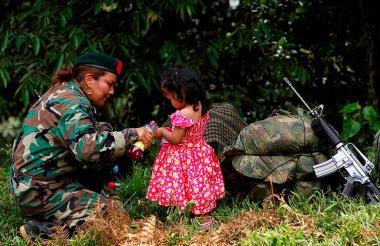Una guerrillera de las Farc juega con una niña este martes en una de las zonas veredales en La Elvira, en las montañas del Cauca.