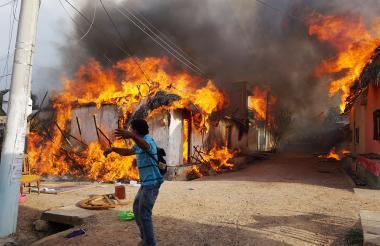 Un hombre trata de apoyar el voraz incendio que consume las cuatro viviendas en Sincé.