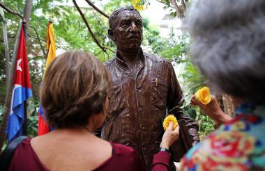 Dos mujeres le ponen flores amarillas al monumento de Gabriel García Márquez develado este jueves en La Habana.