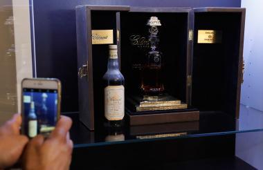 Una persona no identificada toma una foto con su móvil a la botella de ron vendida en Francia.
