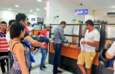 El secretario de Tránsito, Víctor Arismendi, de camisa gris, en momentos en que pagaba la multa.