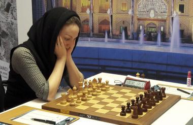 Un mujer con el velo juega ajedrez.