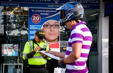 Un policía aplica un comparendo a un motociclista por incumplir la norma.