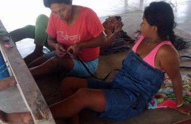 Las tres mujeres con un pie metido en el cepo como castigo.