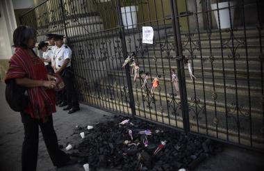 Una mujer observa las muñecas que fueron ubicadas en la entrada del hogar donde fallecieron las 33 adolescentes.