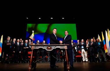 El presidente Juan Manuel Santos y el líder de las Farc, Rodrigo Londoño, 'Timochenko', se saludan en la firma del Acuerdo Final de Paz, el pasado 24 de noviembre en el Teatro Colón.