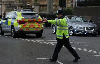 Un policía controla el tráfico en la zona cercana al Parlamento Británico.