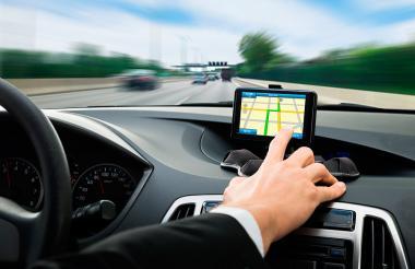 Hombre utilizando un GPS mientras maneja un carro.