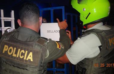 Dos uniformados pegan el cartel de 'sellado' en uno de los establecimientos cerrados por diez días.