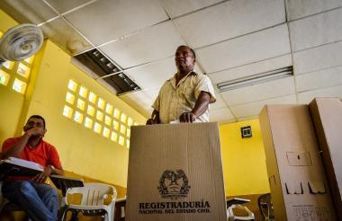 Un sufragante deposita su voto en la urna, en un solitario salón.