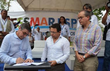 El gerente de Metroagua, Juan Luis Londoño, firma el acta de entrega de las redes de agua y alcantarillado a la Alcaldía Distrital. Observan el mandatario seccional Rafael Martínez y el procurador General, Fernando Carrillo.