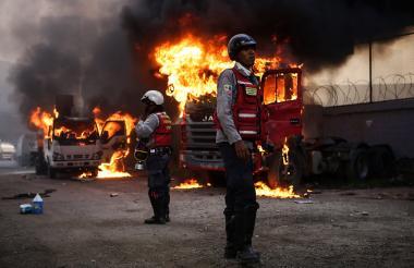 Policías observan dos camiones del Ministerio de Transporte incendiados este lunes por manifestantes al este de Caracas.