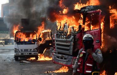 Un manifestante se aleja debido al incendio de dos vehículos ayer en Caracas.