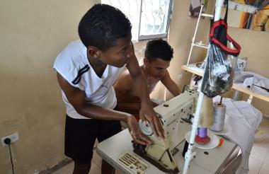 Luis Pereira da vueltas manualmente a la volanta de la máquina de coser ante la falta de energía eléctrica.