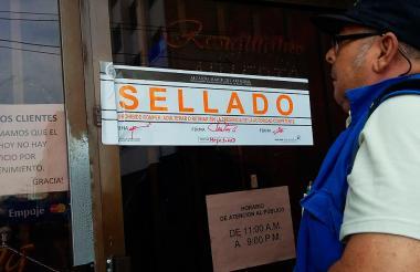 """Un funcionario del Dadis observa el letrero de """"Sellado"""" en el restaurante Dragon King."""