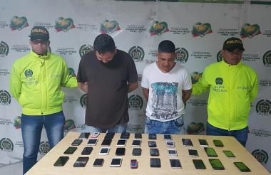 Los detenidos junto a parte de los celulares incautados.