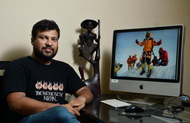 El alpinista Satyarup Siddhanta posa junto al computador que muestra la foto que él se tomó en la cima del Everest. Esa imagen fue usada por la pareja de farsantes para hacer un montaje y simular su presencia en la montaña más alta del planeta.