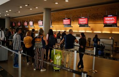 Personas hacen fila en módulos de aerolíneas en una terminal aérea.